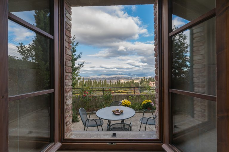 Window on the terrace of an apartment overlooking the countryside of Tuscany